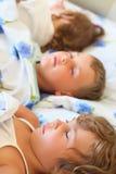 Niños tres junto que duermen en cama Fotos de archivo libres de regalías