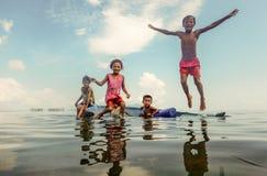 Niños tribales de Bajau que se divierten saltando en el mar de su barco, Sabah Semporna, Malasia Imagen de archivo