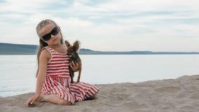 Niños uno que se sientan en la playa y el perro Imagenes de archivo