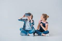 Niños usando las auriculares de la realidad virtual mientras que se sienta en el piso Foto de archivo