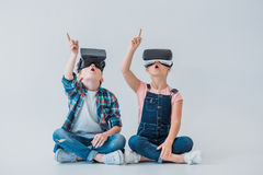 Niños usando las auriculares de la realidad virtual y el destacar con el finger mientras que se sienta en el piso Fotografía de archivo libre de regalías