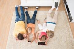 Niños usando las tabletas que mienten en la alfombra foto de archivo libre de regalías