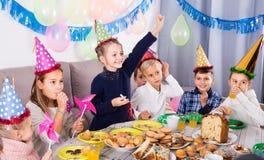Niños vigorosos que tienen un buen rato en una fiesta de cumpleaños Fotos de archivo libres de regalías