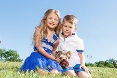 Niños vivaces que se divierten con el perro Fotografía de archivo libre de regalías