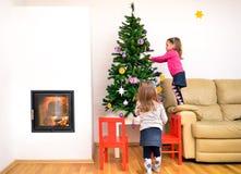 Niños y árbol de navidad en el apartamento de lujo moderno con el fuego Foto de archivo