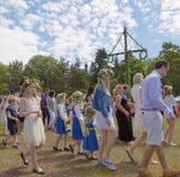 Niños y adultos que bailan alrededor del Maypole que celebra el S imagen de archivo