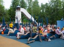 Niños y adultos que descansan sobre el patio Imágenes de archivo libres de regalías