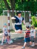 Niños y adultos que juegan al fútbol en parque junto fotografía de archivo