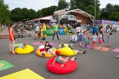 Niños y adultos que juegan y que mienten en los colchones inflables Imagenes de archivo