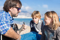 Niños y canción del canto del padre en la playa Foto de archivo