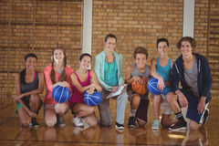 Niños y coche de la High School secundaria que se arrodillan con baloncesto en la corte Foto de archivo libre de regalías