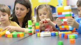 Niños y educador Playing en la guardería metrajes