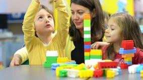 Niños y educador Playing en la guardería