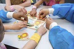 Niños y enfermeras que juegan con rompecabezas Imágenes de archivo libres de regalías