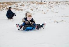 Niños y juego del padre en la nieve Foto de archivo