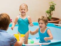 Niños y madre que juegan en piscina imagenes de archivo