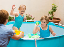 Niños y madre que juegan en piscina Fotografía de archivo