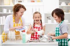 Niños y madre que lavan los platos Imagen de archivo libre de regalías