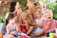 Niños y madres en el partido de té al aire libre Imagenes de archivo