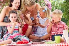 Niños y madres que comen la torta en Outd Fotografía de archivo libre de regalías