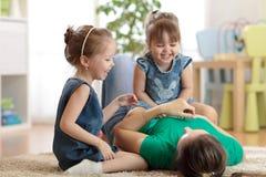 Niños y mamá sonrientes que tienen un pasatiempo de la diversión en piso en sitio de niños en casa imagen de archivo
