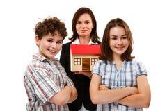 Niños y modelo de la casa aislados en el fondo blanco Foto de archivo