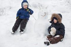 Niños y muñeco de nieve Imágenes de archivo libres de regalías