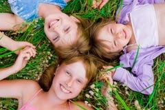 Niños y muchachas bonitos del adolescente en hierba verde Fotos de archivo libres de regalías