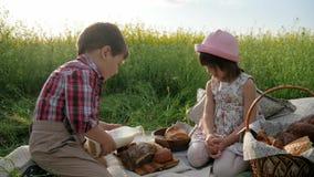 Niños y naturaleza, amigos en césped verde, comida campestre, muchacho y muchacha con la comida en la naturaleza, niños felices e metrajes