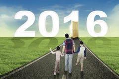 Niños y padre que caminan hacia los números 2016 Imágenes de archivo libres de regalías