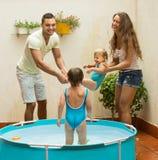 Niños y padres que juegan en piscina Fotografía de archivo libre de regalías