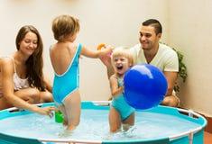 Niños y padres que juegan en piscina Fotos de archivo