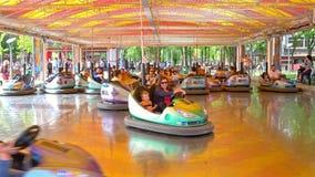 Niños y padres que se divierten en paseo de los coches de parachoques metrajes