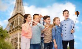 Niños y palillo del selfie del smartphone sobre torre Eiffel Imágenes de archivo libres de regalías