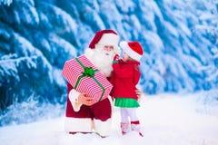 Niños y Papá Noel con los regalos de Navidad Imagenes de archivo