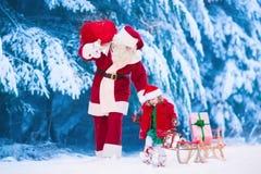 Niños y Papá Noel con los regalos de Navidad Imágenes de archivo libres de regalías