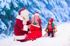 Niños y Papá Noel con los regalos de Navidad Fotografía de archivo libre de regalías