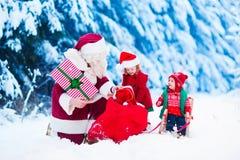Niños y Papá Noel con los regalos de Navidad Fotos de archivo libres de regalías