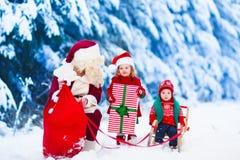 Niños y Papá Noel con los regalos de Navidad Imagen de archivo libre de regalías