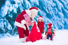 Niños y Papá Noel con los regalos de Navidad Fotos de archivo