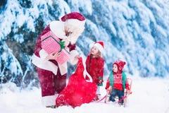 Niños y Papá Noel con los regalos de Navidad Foto de archivo libre de regalías