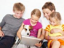 Niños y perro con la tableta Imagen de archivo libre de regalías