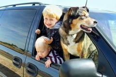 Niños y perro en minivan Fotos de archivo libres de regalías