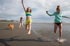 Niños y perro que corren en la playa Imagen de archivo