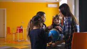 Niños y profesor diversos con el globo en guardería almacen de metraje de vídeo