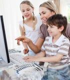 Niños y su madre que usa un ordenador Foto de archivo libre de regalías
