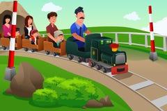 Niños y sus padres que montan un pequeño tren Imagenes de archivo