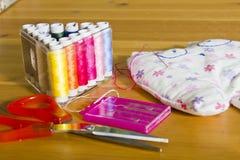Nić, igły, nożyce i zabawka na stole, Fotografia Stock