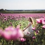 Ni?a adorable con el pelo largo en caminar solo del vestido blanco en el campo de Poppy Flowers de la lila fotos de archivo libres de regalías