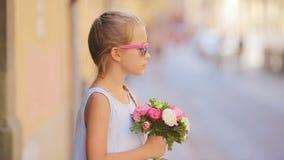 Ni?a adorable con el ramo de las flores que camina en ciudad europea al aire libre almacen de video